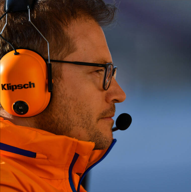 Mc Laren crew member wearing a headset with a Klipsch logo Mobile